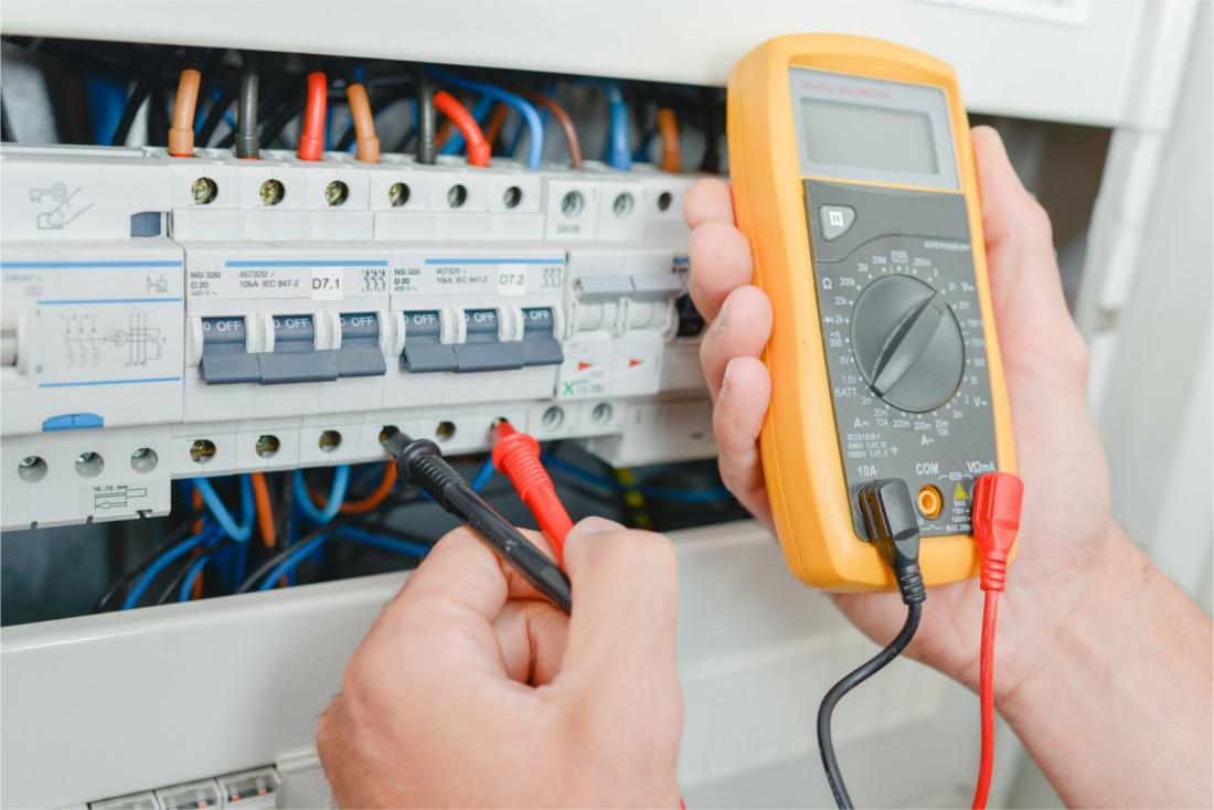 Electrician measuring voltage using multimeter